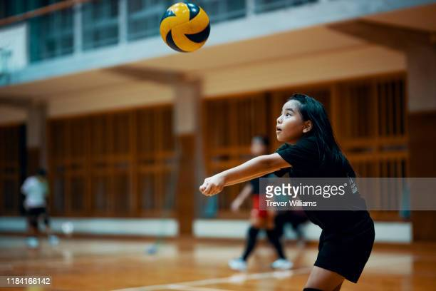 young girl playing volleyball at a team practice in a school gym - termine sportivo foto e immagini stock