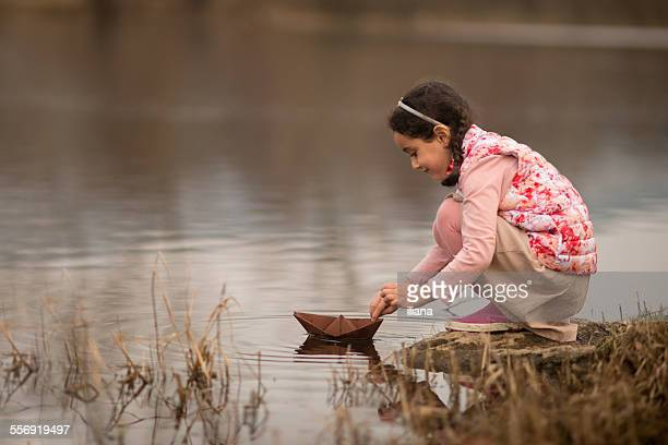 Young girl playing with a paper boat