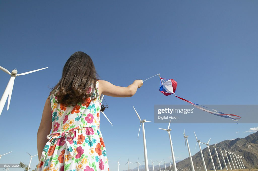 Young Girl Playing With a Pinwheel in a Wind Farm : Stock Photo