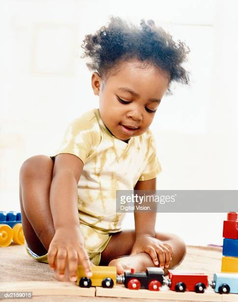 Young Girl Playing with a Toy Train Set