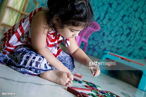 Young girl playing with alphabet letters