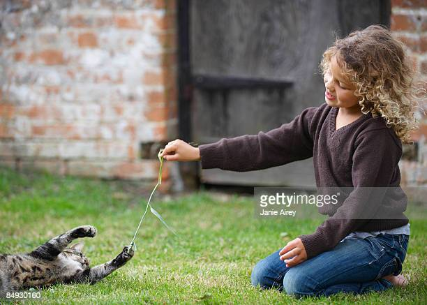 Young girl playing with cat outside
