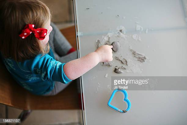 Young girl playing with clay