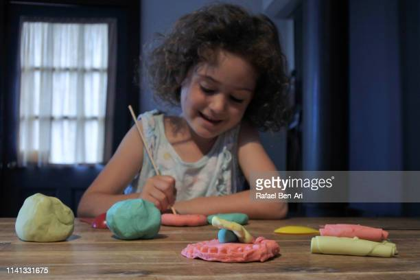 Young girl playing with colorful playdoh
