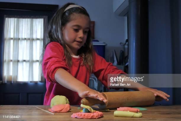 young girl playing with colourful playdoh - rafael ben ari stock-fotos und bilder