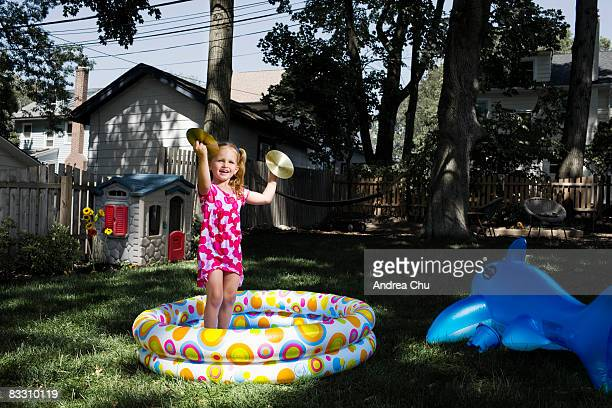 Young girl playing with cymbals in a kiddy pool.