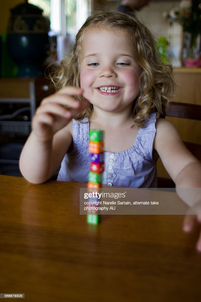Young girl playing with dice tower : Stock Photo