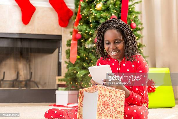 Young girl playing with digital tablet on Christmas morning