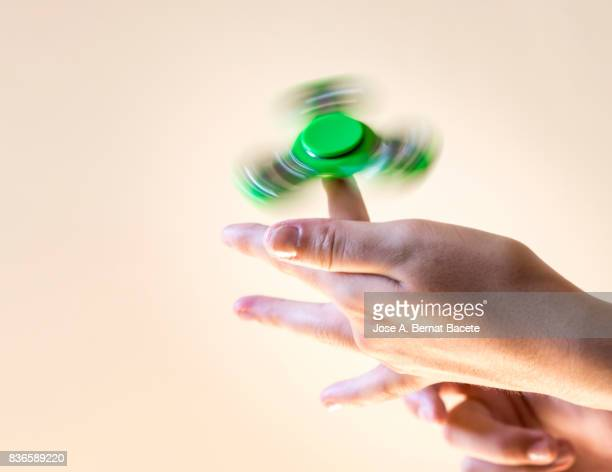 Young girl playing with fidget spinner toy to relieve stress . Spain