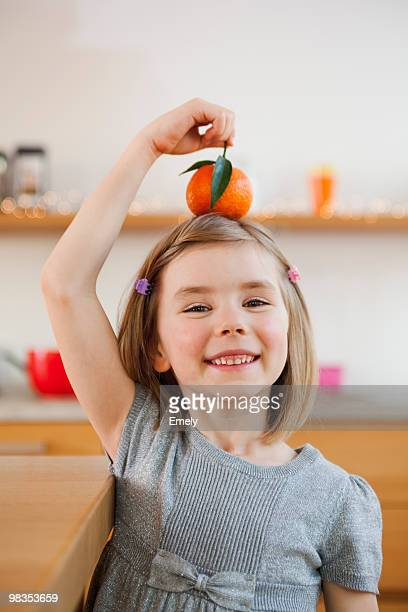 young girl playing with fruit