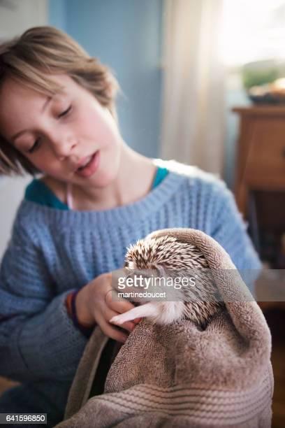 Ung flicka som leker med igelkott husdjur i hennes sovrum.