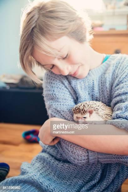 Jong meisje spelen met egel huisdier in haar slaapkamer.