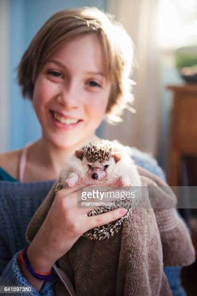 Young girl playing with hedgehog pet in her bedroom.