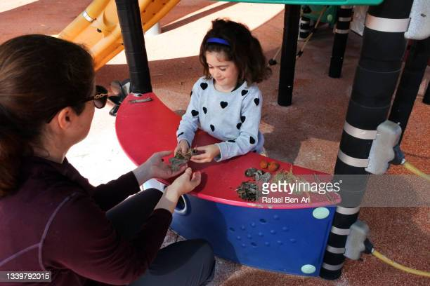 young girl playing with her mother pretending to have a cafe restaurant - rafael ben ari stock-fotos und bilder