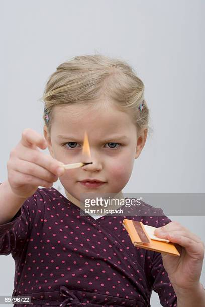 A young girl playing with matches