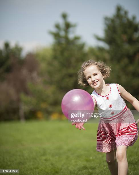 Young girl playing with purple ball in the park