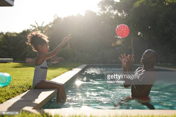 Young girl playing with red ball with her father in pool