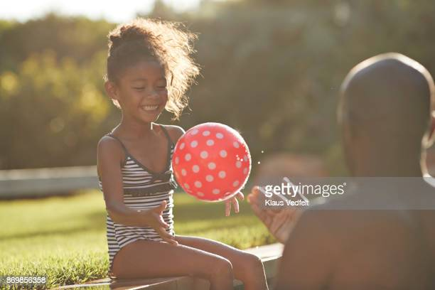 young girl playing with red ball with her father in pool - day 7 - fotografias e filmes do acervo