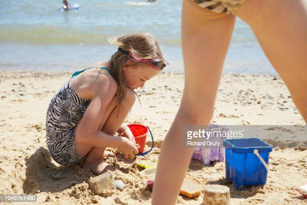 Young girl playing with sand at the beach