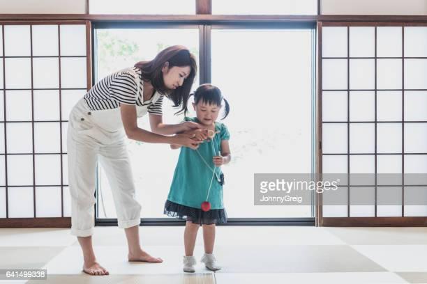 家で彼女の母親と一緒におもちゃで遊ぶ少女