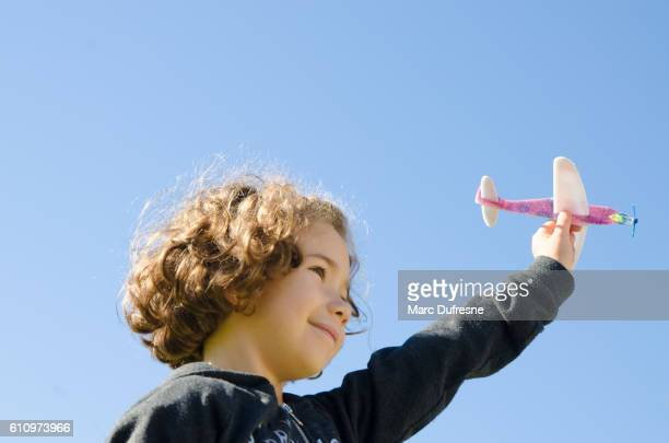 Young girl playing with toy plane