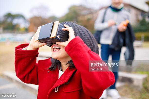 Young girl playing with virtual reality simulator with father