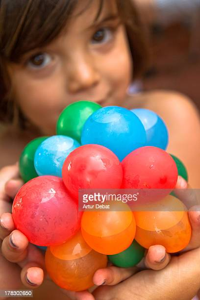 Young girl playing with water balloon at house
