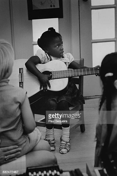 A young girl plays a guitar in front of classmates during a Head Start Program class held at San Jose State College San Jose California 1965
