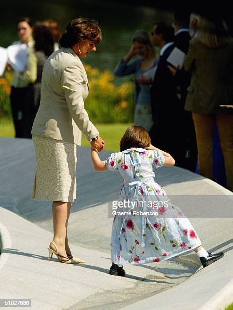 A young girl plays in the fountain as HM Queen Elizabeth IIand most of the Royal family together with the Spencers attend the opening of the Diana...