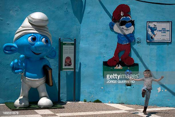 """A young girl plays in the village of Juzcar near Malaga southern Spain on May 23 2013 'The Smurfs 2' a sequel to """"The Smurfs"""" a movie on animated..."""