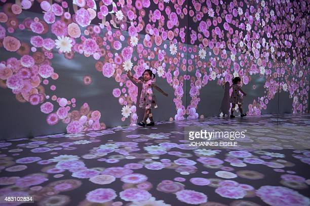 A young girl plays next to flowers projected onto a wall and mirrors during a promotional campaign at a shopping mall in Shanghai on August 6 2015...