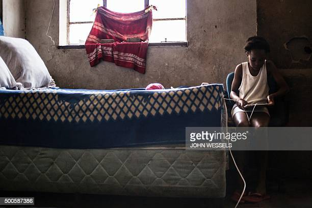 A young girl plays on her tablet in a squat on November 24 2015 in Hillbrow Johannesburg Taken over buildings are a common feature in downtown...