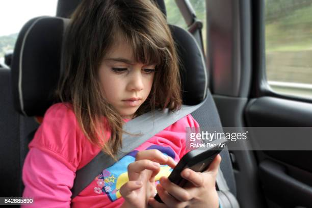 Young girl plays on mobile phone  in a car