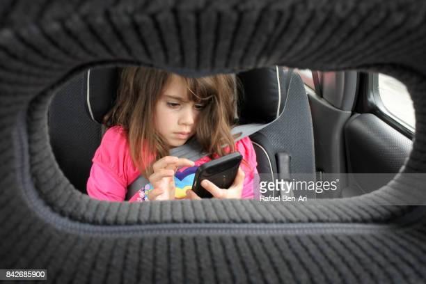 young girl plays on mobile phone  in a car - rafael ben ari imagens e fotografias de stock