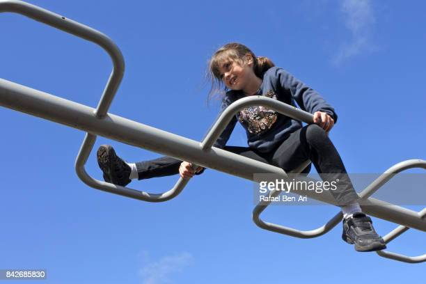 young girl plays on monkey bars - monkey shoes stock photos and pictures