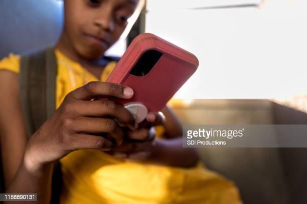 若い女の子がスマートフォンで遊ぶ - 乗り物に乗って ストックフォトと画像