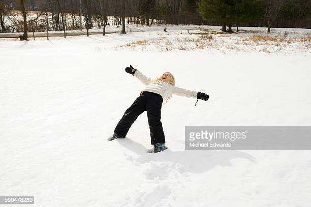 Young girl plays snow angel