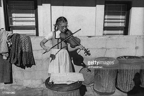 A young girl plays the violin amongst bins on the street circa 1980