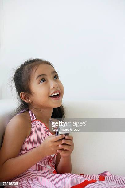 A young girl plays with a cellphone