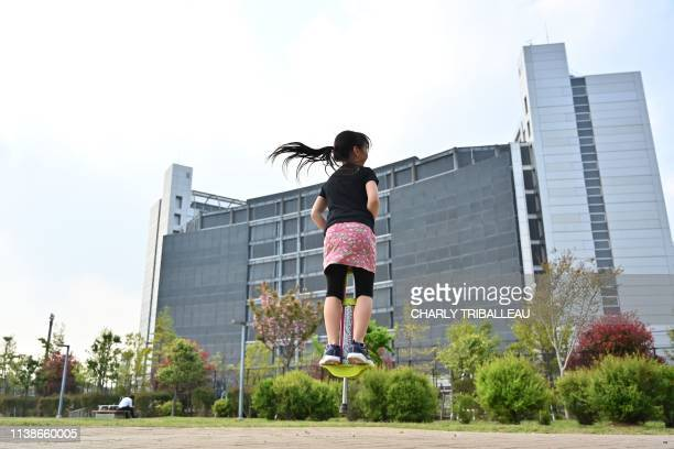 Young girl plays with a pogo stick in front of the Tokyo Detention House where former Nissan chairman Carlos Ghosn is detained in Tokyo on April 22,...
