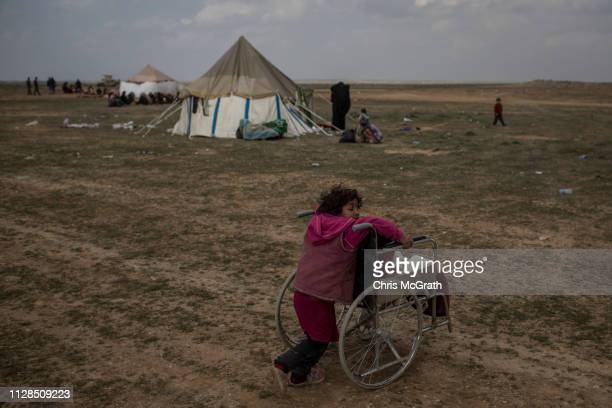 Young girl plays with a wheelchair as her family, who have fled fighting in Bagouz wait to board trucks after being screened by members of the Syrian...