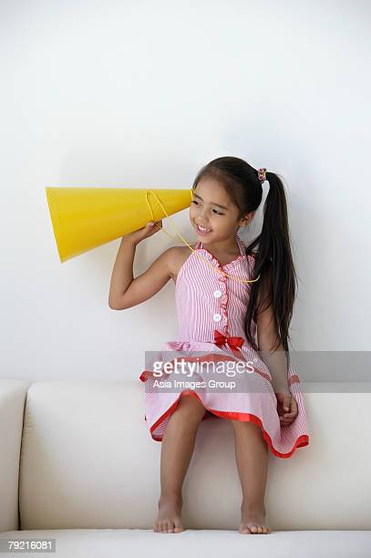 A young girl plays with a yellow cone