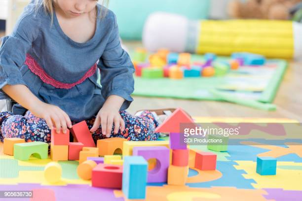 Young girl plays with building blocks during preschool class
