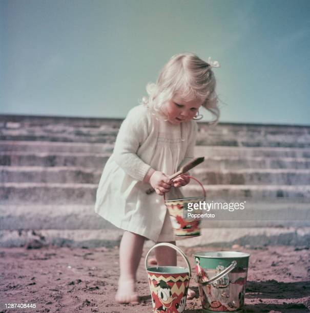 Young girl plays with her buckets and spade on the beach at the seaside town of Torquay in Devon, England in May 1949.