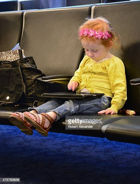 A young girl plays with her digital tablet as she and her family wait for their flight in the boarding gate area at LaGuardia Airport in New York...
