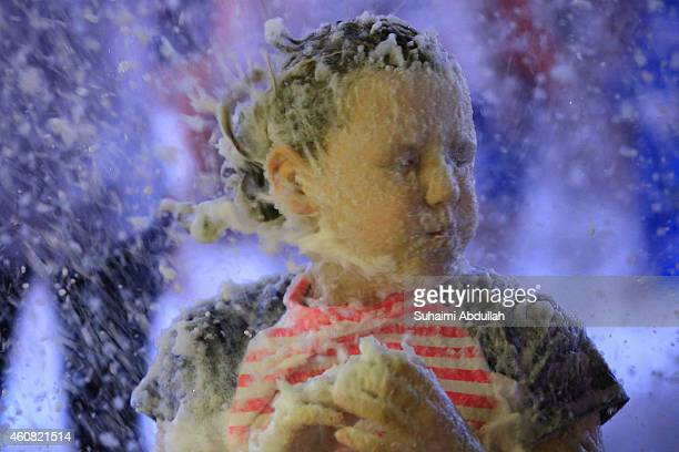 A young girl plays with the artificial snow made of foam at Tanglin Mall shopping centre on December 24 2014 in Singapore The mall has been holding...