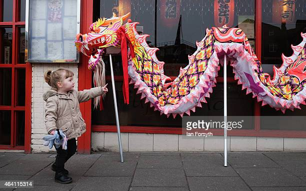 A young girl points at a ceremonial dragon leaning against a shop front as the Chinese community come together to welcome in the Chinese New Year on...