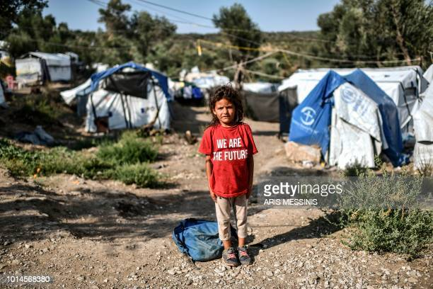 Young girl poses at a camp next to the Moria refugee camp in the island of Lesbos on August 5, 2018.