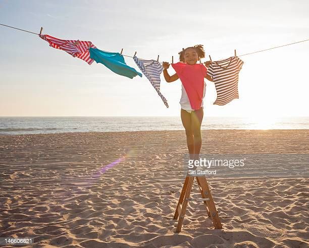 Young girl poses behind a t-shirt on clothesline