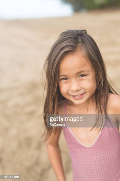 Young ethnic girl poses for a picture on Hawaiian beach.